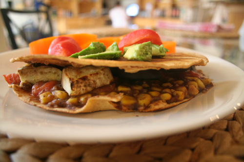 A wrap stuffed with beans, corn, eggplant, and tomato.