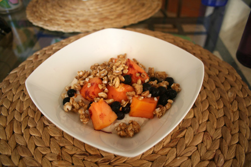 Fig yogurt topped with papaya chunks, blueberries, and granola.