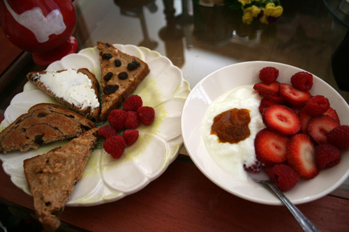 Cinnamon raisin toast with various toppings. Yogurt with sliced strawberries and pumpkin butter.
