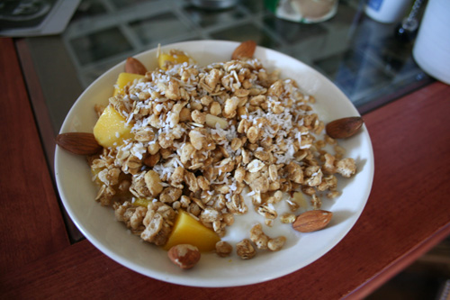 A delicious bowl of Zoe's Honey Almond granola with extra almonds and mango over yogurt.